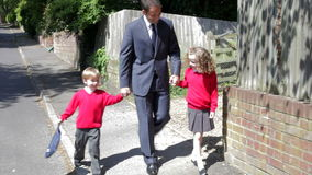 Padre Walking To School con los niños en manera de trabajar almacen de metraje de vídeo