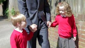 Padre Walking To School con los niños en manera de trabajar almacen de video