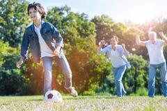 Padre y abuelo que animan para el nieto que juega a fútbol Imagen de archivo