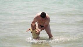 Padre y bebé en el swimsuite amarillo que juega en el mar Atenas Grecia paternidad almacen de metraje de vídeo