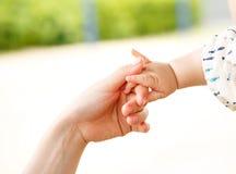 Padre y bebé que mantienen la mano unida Imagen de archivo libre de regalías