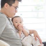 Padre y bebé que se sientan en el sofá imagen de archivo