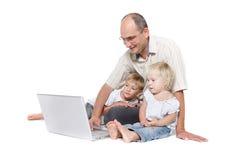 Padre y dos cabritos con la computadora portátil imagen de archivo