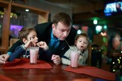 Padre y dos hijos que beben el batido de leche fotos de archivo