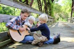 Padre y dos niños que juegan la guitarra afuera en el parque Imagen de archivo libre de regalías