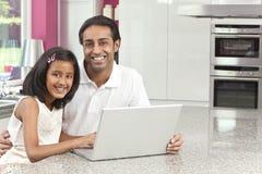Padre y hija indios que usa el ordenador portátil Foto de archivo