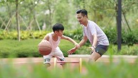 Padre y hijo asiáticos que juegan a baloncesto en jardín por la mañana en la cámara lenta almacen de video