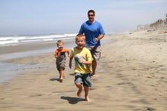 Padre y hijos felices en la playa Fotos de archivo