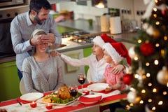 Padre y madre de las sorpresas de los niños con el dinne de la Navidad de la familia Imágenes de archivo libres de regalías