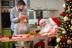 Padre y madre de las sorpresas de los niños con la cena de la Navidad Foto de archivo libre de regalías
