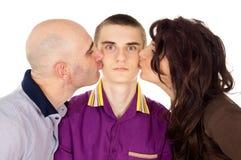 Padre y madre que besan a su hijo Imágenes de archivo libres de regalías