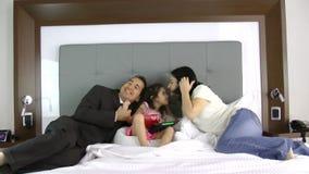 Padre y madre que dan un regalo a su pequeña hija en el dormitorio metrajes