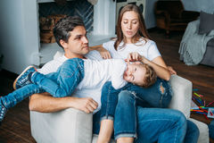 Padre y madre que mienten en el sofá y que juegan con dos pequeños hijos Foto de archivo