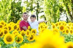 Padre y muchacho en un campo de los girasoles Imágenes de archivo libres de regalías