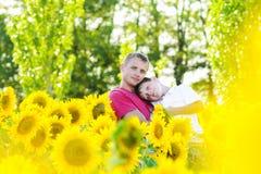 Padre y muchacho en un campo de los girasoles Imagenes de archivo