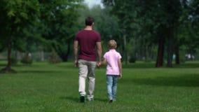 Padre y muchacho que llevan a cabo las manos, yéndose, dando el consejo para que hijo sea hombre real metrajes