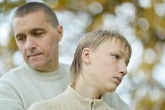 Padre y muchacho tristes imagenes de archivo