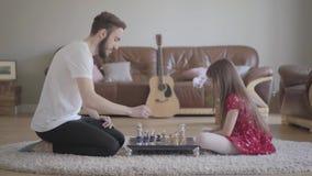Padre y niña barbudos jovenes con el pelo largo que juega al ajedrez que se sienta en el piso en la alfombra mullida delante de almacen de video