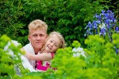 Padre y niña felices en un jardín imagen de archivo