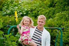 Padre y niña felices en un jardín imagenes de archivo