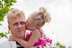 Padre y niña felices en un jardín fotos de archivo