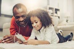 Padre y niño alegres usando el teléfono móvil con los auriculares imagen de archivo