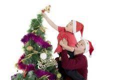 Padre y niño con el árbol de navidad en estudio Imágenes de archivo libres de regalías