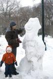 Padre y niño con el muñeco de nieve Foto de archivo libre de regalías