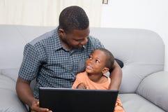Padre y niño con un ordenador portátil Imágenes de archivo libres de regalías