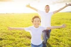 Padre y niño de la familia que corren en prado foto de archivo