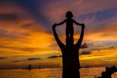 Padre y niño en fondo del mar de la puesta del sol Fotografía de archivo