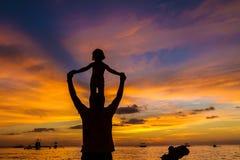 Padre y niño en fondo del mar de la puesta del sol Foto de archivo