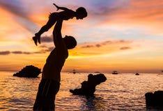 Padre y niño en fondo del mar de la puesta del sol Imagen de archivo libre de regalías