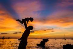Padre y niño en fondo del mar de la puesta del sol Foto de archivo libre de regalías