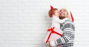 Padre y niño felices de la familia con el regalo en beso de la Navidad Imagenes de archivo