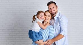 Padre y niño felices de la madre de la familia cerca de una pared de ladrillo vacía imagen de archivo