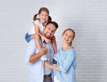 Padre y niño felices de la madre de la familia cerca de una pared de ladrillo vacía Fotografía de archivo libre de regalías