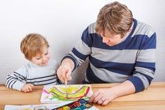 Padre y niño pequeño que tienen pintura de la diversión Imagenes de archivo