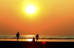 padre y niño por la orilla de mar, puesta del sol Foto de archivo