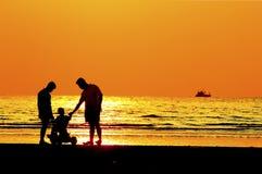Padre y niño por la orilla de mar, puesta del sol Fotografía de archivo libre de regalías