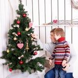 Padre y niño que adornan el árbol de navidad Imágenes de archivo libres de regalías