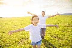 Padre y niño que corren en prado imagenes de archivo