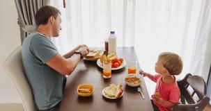 Padre y niño que gozan del desayuno almacen de video