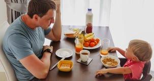 Padre y niño que gozan del desayuno metrajes