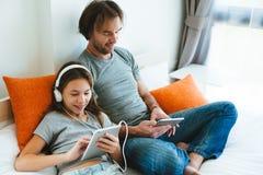 Padre y niño que juegan en la tableta Foto de archivo