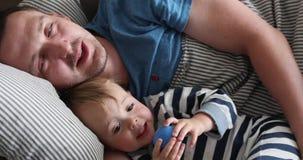 Padre y niño que mienten en cama en primer de la mañana almacen de video