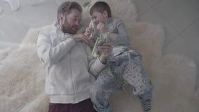 Padre y niño recoger el dinero dispersado en el piso Papá y niño del entretenimiento relación del Padre-niño Cámara lenta almacen de video