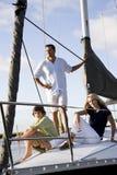 Padre y niños adolescentes en el barco de vela en el muelle Imagenes de archivo