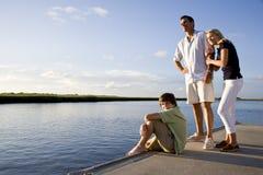 Padre y niños adolescentes en muelle por el agua Imagen de archivo
