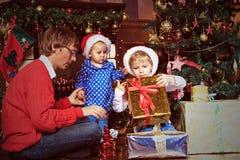 Padre y niños con los presentes en la Navidad Imagenes de archivo